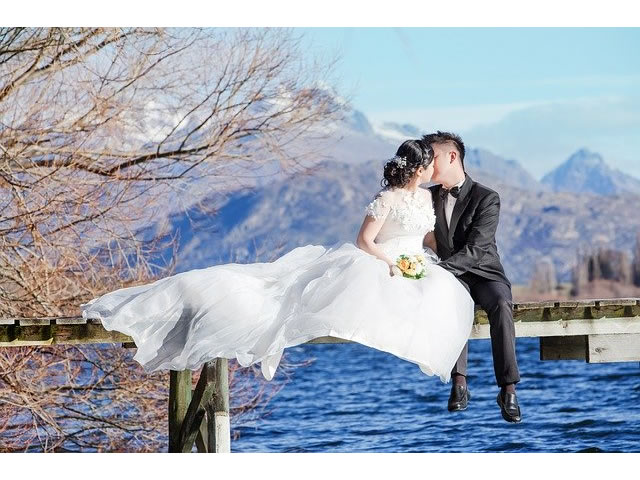 Newlyweds kissing on a deck above the water